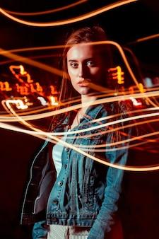 Affascinante modella bruna in posa con tecnica di luce mista nel viale notturno