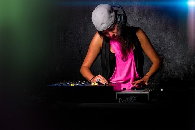 Ragazza affascinante deejay al lavoro che mescola il suono sulla sua console all'ap