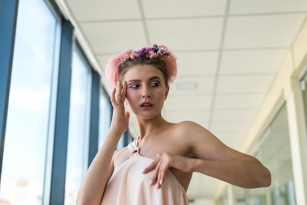 Signora affascinante con il trucco alla moda in posa direttamente alla telecamera