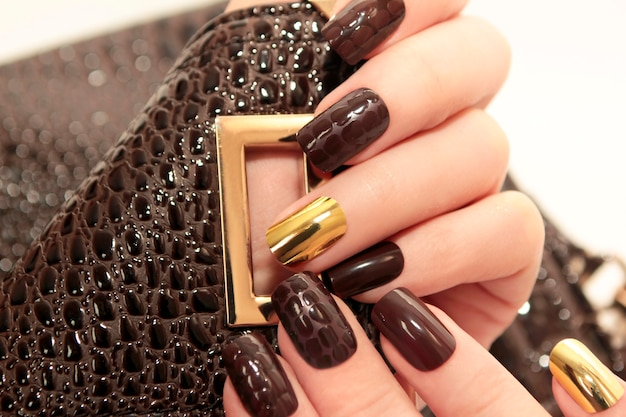 Manicure glamour lussuoso coccodrillo marrone con unghie da donna placcate in oro closeup