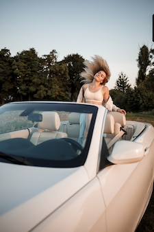 Una ragazza di lusso affascinante con i capelli biondi che sorride mentre è seduta su una decappottabile bianca. giovane donna di successo seduta nella sua macchina bianca