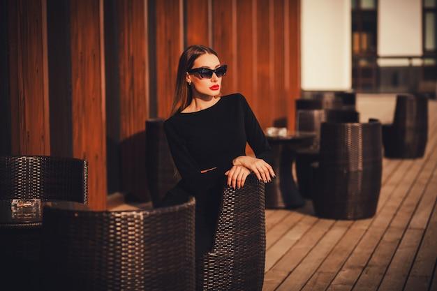 Ritratto affascinante di una donna alla moda in un caffè.