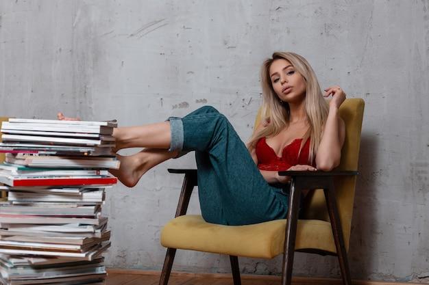 La giovane donna sexy affascinante con capelli biondi in un reggiseno di pizzo elegante rosso in jeans alla moda sta riposando in studio su una sedia morbida vintage vicino a una pila di giornali e riviste.