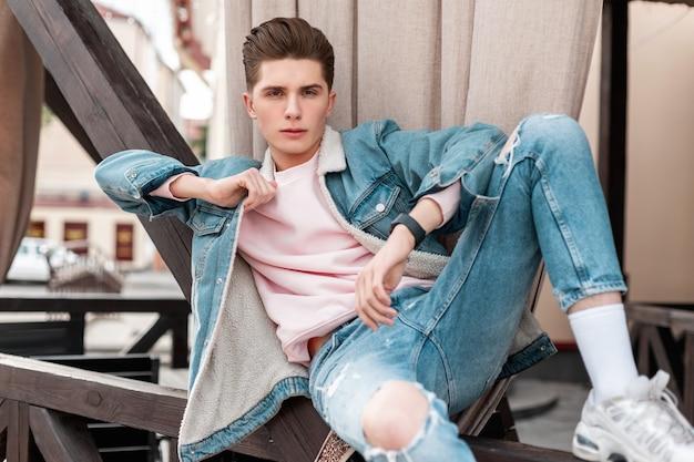 Giovane alla moda affascinante in jeans strappati in giacca di jeans blu, scarpe da ginnastica bianche alla moda riposano su tavole di legno in città all'aperto. modello di moda ragazzo europeo in abiti casual vintage su strada.