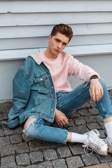 Affascinante modello urbano giovane con acconciatura in giacca di jeans in jeans vintage in felpa elegante rosa resto vicino a edificio d'epoca in città. bel ragazzo sedersi su piastrelle di pietra in strada. moda giovanile.