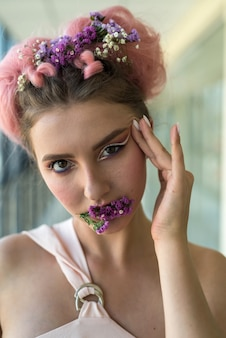 Donna affascinante in abiti beige contro il muro con trucco alla moda