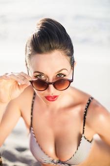 Donna affascinante in bikini che osserva sopra gli occhiali da sole