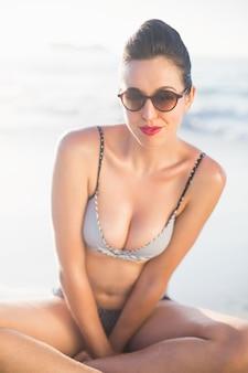 Donna affascinante in bikini che si siede sulla spiaggia