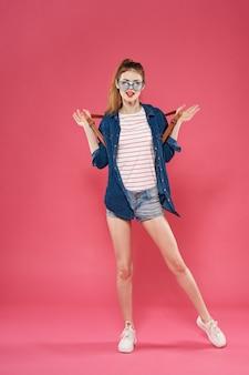 Affascinante donna glamour alla moda vestiti ritagliata vista sfondo rosa. foto di alta qualità
