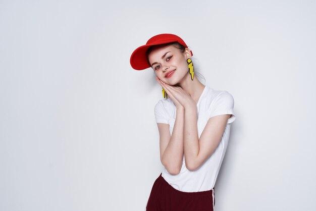 Donna affascinante nella decorazione di moda estiva con berretto rosso in posa sfondo chiaro