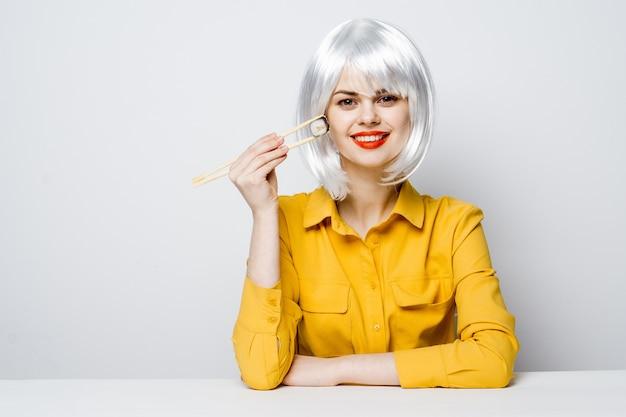 Affascinante donna in parrucca bianca labbra rosse tenere snack rotoli con le bacchette. foto di alta qualità
