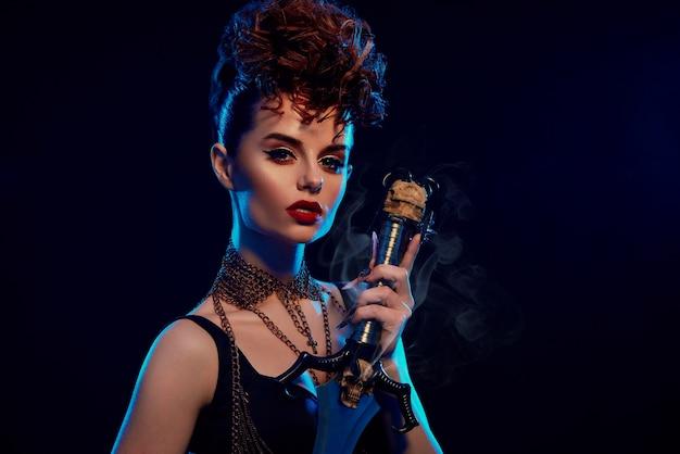 Donna affascinante con hairdress alla moda che tiene la spada d'acciaio.