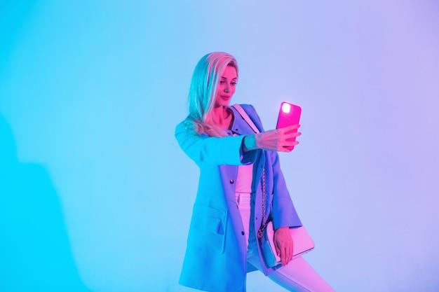 La ragazza affascinante in vestiti luminosi alla moda con una borsa alla moda fa una foto del selfie su uno smartphone in studio su una luce al neon colorata