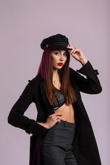 Il modello di moda affascinante della giovane donna con le labbra rosse con capelli lunghi in cappotto nero alla moda raddrizza il cappuccio elegante vicino alla parete rosa nello studio. moderna ragazza bruna sexy in abiti classici al chiuso.