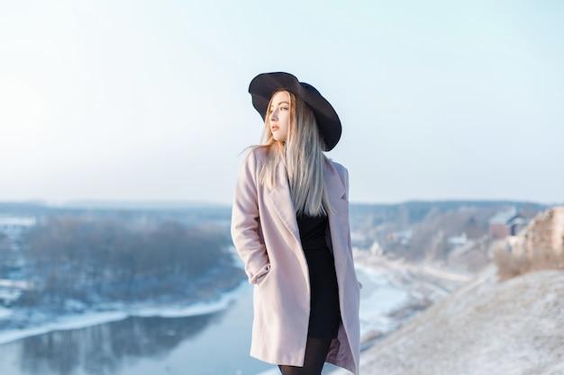 La giovane donna affascinante in un cappotto rosa alla moda in un cappello elegante in un vestito lavorato a maglia nero sta levandosi in piedi su una montagna