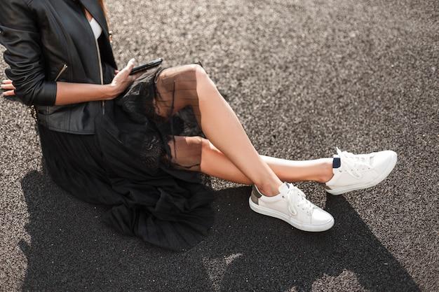 Affascinante giovane donna in scarpe da ginnastica alla moda bianche in una giacca di pelle vintage in una gonna elegante con un telefono cellulare si siede sull'asfalto in una giornata di sole. collezione di abbigliamento autunnale delle donne. avvicinamento.