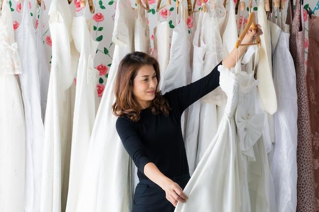 Glamour donna asiatica sposa proprietario del negozio di nozze che lavora nel suo studio, selezionando e rivedendo i vestiti e l'abito da sposa con la faccia sorridente e la felicità. concetto di designer e imprenditore.