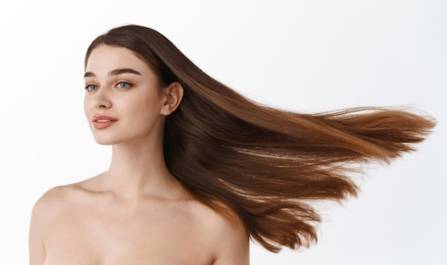 Glamour bella donna castana con capelli castani sani e di bellezza isolati su muro bianco