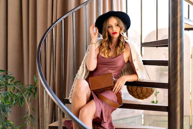 Glamour elegante bionda riccia beata donna bionda in posa sulle scale, elegante abito da sera e trucco