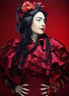 Modello di moda glamour in costume rosso eleganza con cappello rosso. studio girato.
