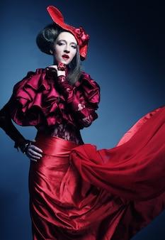 Modello di moda glamour in costume rosso eleganza con cappello rosso