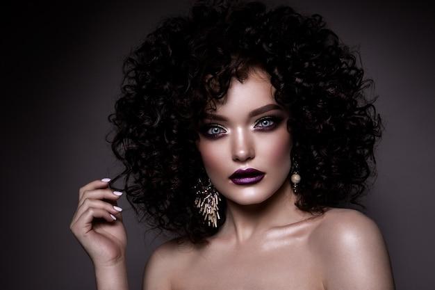 Signora glamour, bella ragazza su sfondo grigio. ritratto. capelli mossi, trucco perfetto. occhi chiusi.