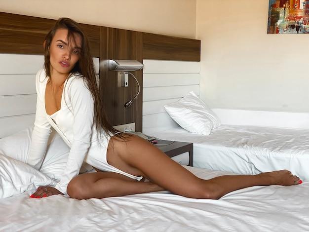 Signora glamour in tuta bianca in posa su un letto nella camera d'albergo