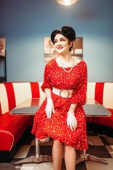 Ragazza pinup glamour con trucco, interni caffè retrò, 50 moda americana. abito rosso con pois, stile vintage