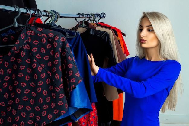 Glamour giovane signora bionda nel negozio di abbigliamento