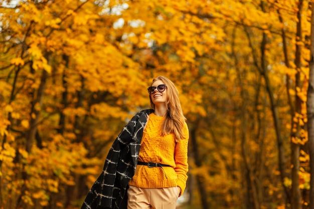 Giovane donna glamour in occhiali da sole rotondi alla moda in elegante abito a righe con spalle sexy con pelle abbronzata sulla strada della spiaggia. modello di ragazza alla moda ritratto all'aperto in una calda giornata di sole