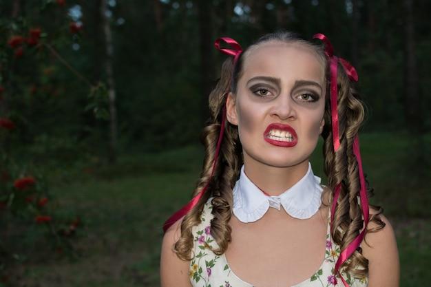 Ragazza di zombie glamour con boccoli come in una bambola. concetto di halloween. foresta di fondo. trucco di halloween.