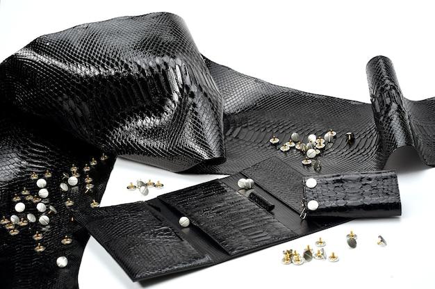 Pezzi di pelle nera glancy giacevano vicino al portafoglio da donna con molti settori. sembrano pelle di rettile. il materiale giace sullo sfondo bianco. inoltre ci sono borchie metalliche vicino ad esso.