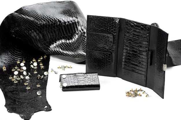 Pezzi di pelle nera glancy giacevano vicino al portafoglio da donna con molti settori. sembrano pelle di rettile. il materiale liscio giace sullo sfondo bianco. inoltre ci sono borchie metalliche vicino ad esso.