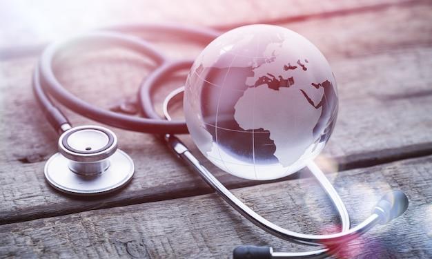 Glasd global e stetoscopio su tavola di legno, concetto di assistenza sanitaria, giornata mondiale dell'ambiente,