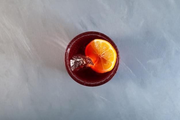 Bicchiere di alcol cocktail negroni americano con arancia e cubetti di ghiaccio vista dall'alto messa a fuoco selettiva copy