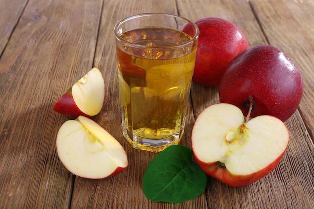Bicchiere di succo di mela con mele rosse sul tavolo di legno, primo piano