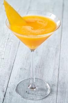 Bicchiere di cocktail mango albicocca guarnito con fetta di mango fresco