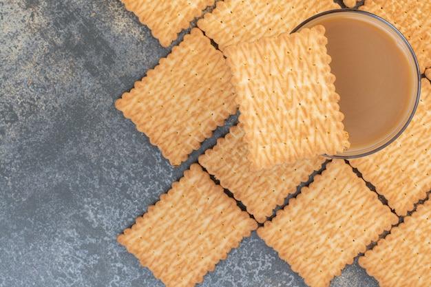 Bicchiere di caffè aromatizzato e gustosi biscotti sulla superficie in marmo.