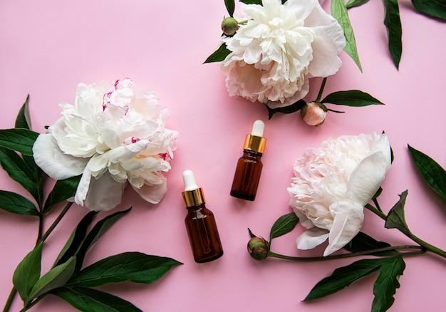 Bottiglie di olio aromatiche in vetro e fiori di peonia su pastello rosa.