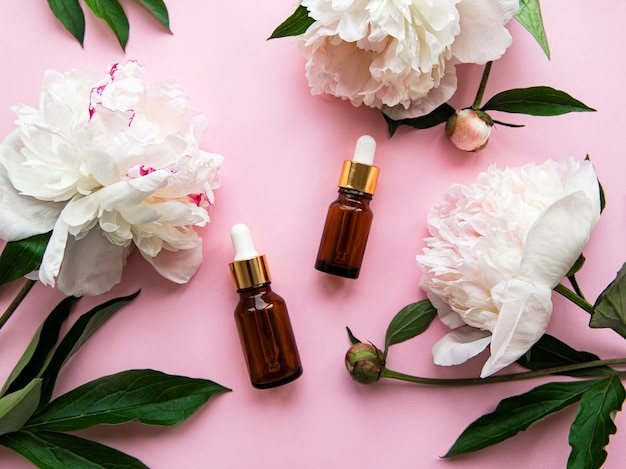 Bottiglie di olio aromatiche in vetro e fiori di peonia su pastello rosa
