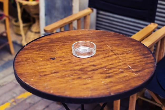 Posacenere in vetro sul tavolo in legno marrone
