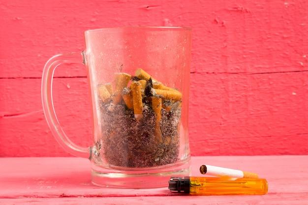 Sigaretta di vetro del portacenere della birra sul colore rosa di legno