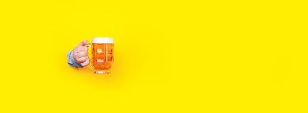 Bicchiere di birra in mano su giallo