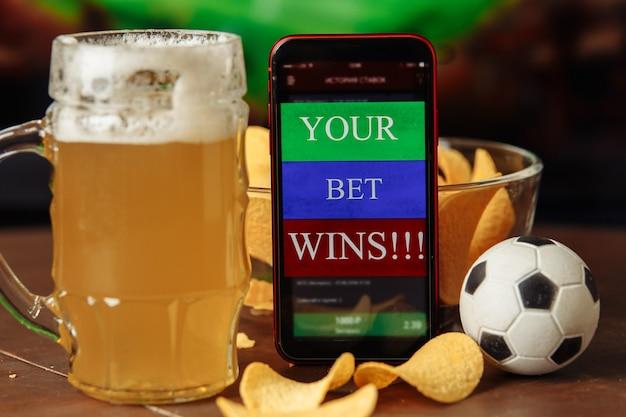 Bicchiere di birra e app mobile per il concetto di scommessa di scommesse