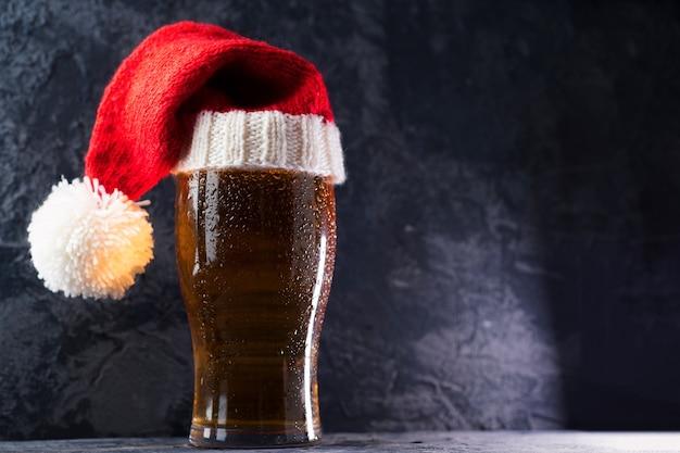Boccale di birra in vetro in cappello di babbo natale