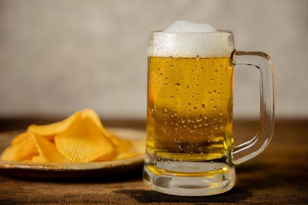 Bicchiere di birra e piatto con poteto chips sul tavolo