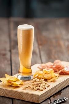Il bicchiere di birra e patatine, pistacchi isolati su un bianco