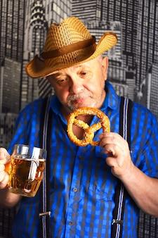 Un bicchiere di birra e un pretzel nelle mani di un uomo.