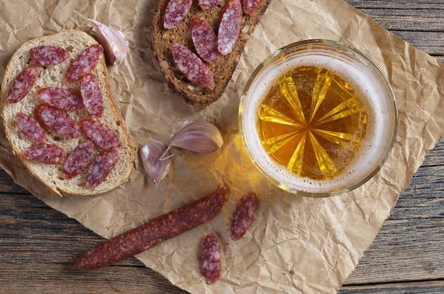 Bicchiere di birra e panini con salsiccia affumicata sottile su carta stropicciata si trova sul vecchio tavolo di legno, vista dall'alto