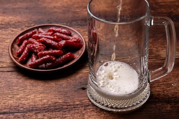 Bicchiere di birra e snack-salsicce secche su uno sfondo di legno. la birra viene versata nel bicchiere.